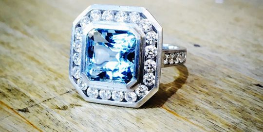 Platinum flush and channel set diamond and aquamarine engagement ring